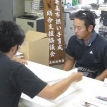 漁業担い手育成支援事業を申請する石山さん(奥)=13日、奄美市役所(提供写真)