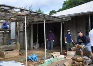力を合わせて改修作業を行うプロジェクトメンバーら=22日、和泊町玉城
