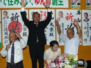 支持者らと喜びの万歳三唱をする山元宗氏(左から2人目)=6日午後10時半ごろ、与論町那間