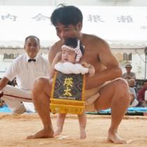 赤ちゃんの土俵入りなどで盛り上った根瀬部町内会の豊年相撲祭=6日、奄美市名瀬