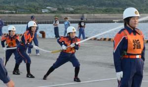 気合の入った表情で放水訓練する女性隊員=5日、和泊町