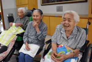 記念品の贈呈式で笑顔を見せる(右から)春山さんと加島さん=15日、喜界町赤連の喜界園