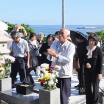 慰霊碑前で犠牲者の冥福を祈る遺族ら=23日、徳之島町