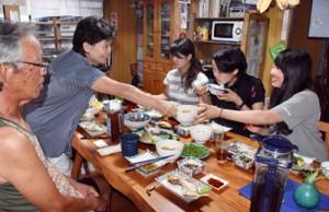 家庭的な雰囲気に包まれた中川さん夫婦と看護学生の夕食=16日、瀬戸内町加計呂麻島三浦