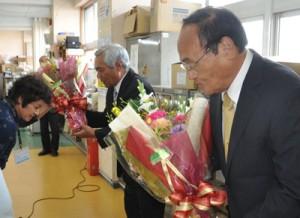 職員から花束を受け取る(手前右から)南町長と川上副町長=24日、与論町役場