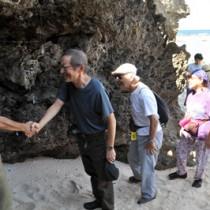 一人一人に首飾りと巡礼冊子が贈られた入島・魂込めの儀式=17日、和泊町国頭の海岸