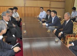 朝山毅市長を訪れ、開校決定を報告する浜崎幸生理事長(右)=8日、奄美市役所