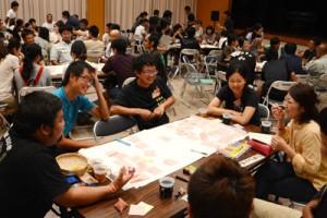 和やかな雰囲気の中、宇検村の将来像について意見を交わした若者たち=24日夜、同村の元気の出る館