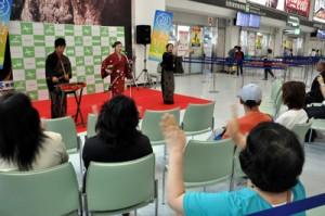 鹿児島空港国内線ビル出発ロビーで島唄を披露する澤愛香さんと「つむぎんちゅ」の2人=5日、霧島市溝辺麓