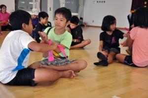 バンダナを使って応急処置を練習する子どもたち=8月30日、和泊町のやすらぎ館