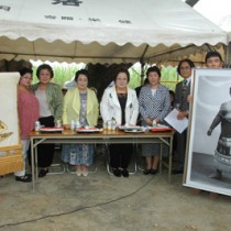 篠川集落に化粧回し(左)を贈った琉王の遺族(正面の女性4人)ら=20日、瀬戸内町篠川