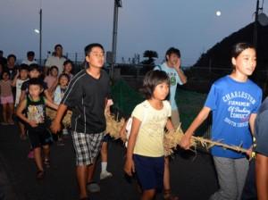 大綱を引いて「十五夜どー、十五夜どー」の掛け声で集落を練り歩く子どもたち=27日、奄美市名瀬小湊