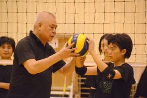 トスで体の使い方を指導する柳本さん(左)=28日、大島高校体育館