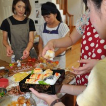 出来上がった料理を盛り付ける参加者ら=23日、奄美市名瀬