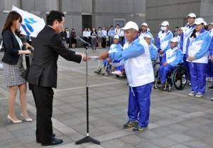 結団式で古川仲二教育長から激励賞を受け取る里島光一郎さん(右)=22日、県庁