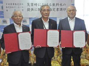 調印後に協定書を披露する朝山市長(中央)と2業者代表=13日、奄美市役所
