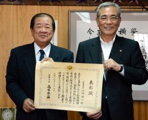 朝山市長に総務大臣表彰受賞を報告した山田さん(写真左)=14日、奄美市役所