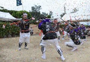 紙吹雪が舞う中で棒踊りを披露する男衆=21日、瀬戸内町実久