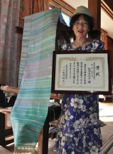 受賞作品「与論の海」と賞状を手に持つ和田美代子さん=与論町