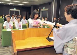 式典で杉村校長(手前)から入学証書を受け取る入学生=10日、奄美市名瀬