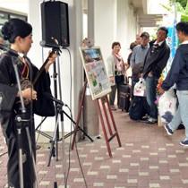 島唄で国文祭参加者らを歓迎する岩元梨恵さん、中村瑞希さん(左から)=30日、奄美空港