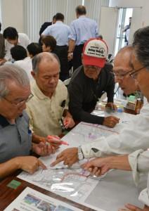 防災研修会で図上訓練に取り組む参加者たち=15日、奄美文化センター