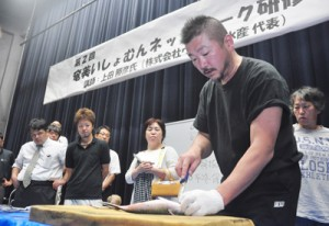 魚食普及について講話し、活け締めの実演も行った上田さん=7日、奄美市名瀬