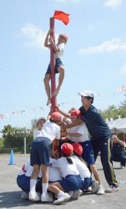 力を合わせ、チームカラーの旗を空高くはためかせる児童ら=4日、龍郷町の龍郷小学校