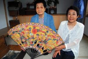 神具の扇を手にノロ祭祀の終わりを残念がる池田オワキさん(左)=6月、大和村今里