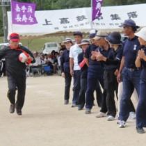 ボールを抱え疾走する仲間に声援を送るチーム=20日、喜界町総合グラウンド