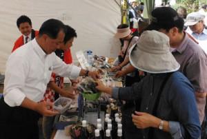 大和村の特産品をPRする伊集院村長(手前左)ら=3日、神奈川県大和市(提供写真)
