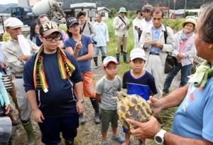 捕獲したアカミミガメを観察する参加者=17日、龍郷町大勝