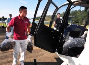 透明袋入りのテックス板のヘリコプターへの積み込み作業(上)と、空中散布のため山間部上空に飛来したヘリコプター=16日、奄美市笠利町