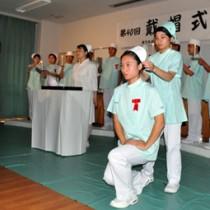 ナースキャップを頭に戴き、決意を新にする衛生看護科の2年生=5日、奄美高校