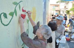 壁面に思い思いに絵を描く参加者=21日、奄美市名瀬矢之脇町