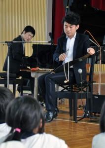 ノコギリ音楽を聞かせるサキタさん(右)=16日、和泊町の国頭小体育館