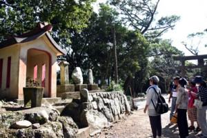 大屯神社で石に刻まれた和歌の意味を考える参加者=21日、瀬戸内町諸鈍