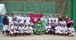 ピッチングマシンと校旗を贈られた奄美高校野球部の生徒ら=29日、奄美高校第2グラウンド
