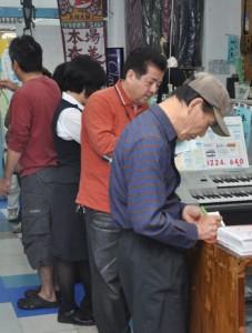 プレミアム商品券を買い求めるため列をつくる市民=2日、奄美市名瀬
