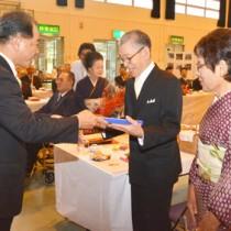 結婚から50年の節目を祝い、伊集院村長から記念品が贈られた大和村の合同金婚式=25日、同村体育館