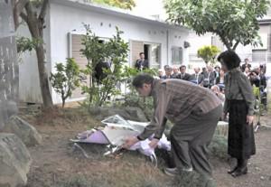 文学碑に献花する潤理事長(手前右)と島尾伸三さん=12日、奄美市名瀬小俣町
