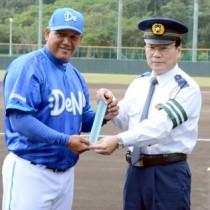 反射材を手にする(左から)ラミレス監督と榊署長=13日、名瀬運動公園市民球場