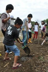 地元小学生とあむとぅの庭づくりに取り組んだ芝浦工業大学の学生ら=3日、伊仙町