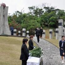 平和の塔に献花する参列者=13日、知名町大山野営場