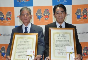 第12回あましん地域貢献賞を受賞した富山氏(左)、大野氏の代理で出席した長男の郁夫氏=4日、奄美市名瀬のホテル