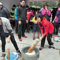 餅つきを楽しむ選手ら=29日、名瀬運動公園陸上競技場