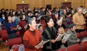奄美群島の日本復帰記念日に「日本復帰の歌」を大合唱する参加者=25日、鹿児島市中央町