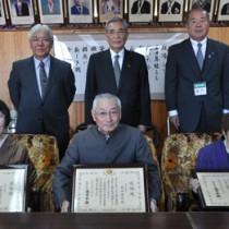 (前列右から)総務大臣表彰を受けた岩崎さんと同感謝状を受けた名島さん、伊集院さん=21日、奄美市役所