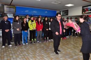 歓迎の花束を受け取るヘッドコーチのイさんと、バドミントン韓国ナショナルチーム=16日、奄美空港