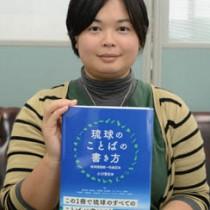 共著「琉球のことばの書き方」を手にする龍郷町出身の重野さん=27日、奄美市名瀬